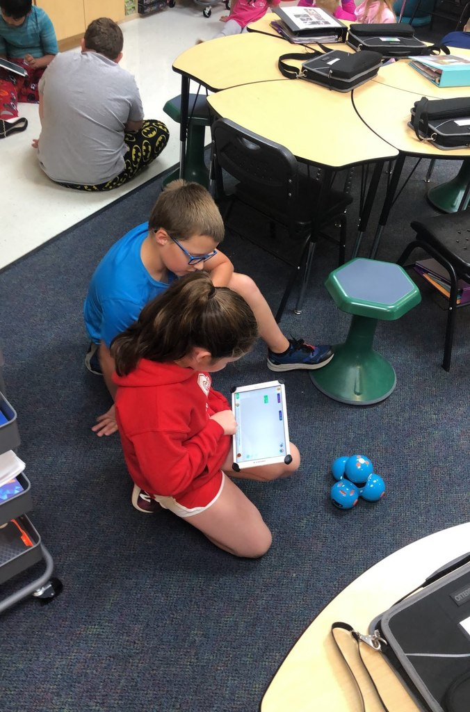 Students using a tablet to provide code for their robots