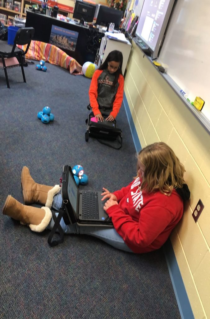 Students using Chromebooks to provide code for their robots